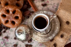 Cup of coffee in turkish cup with spices.