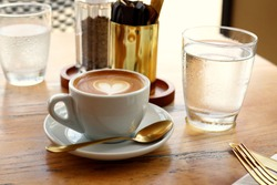 Cup of Coffee in White Mug on Table With Gold Cutlery