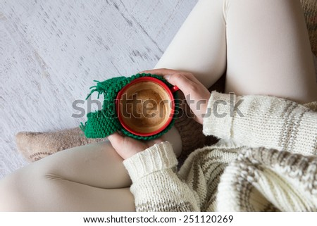 Cup of coffee in woman\'s hands, top view