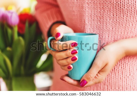 Cup of coffee in woman's hands with bright pink manicure #583046632