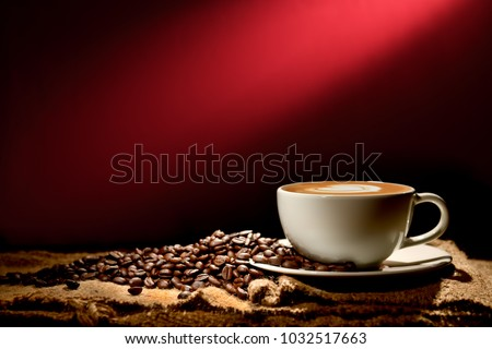 Cup of coffee latte and coffee beans on reddish brown background                                          #1032517663
