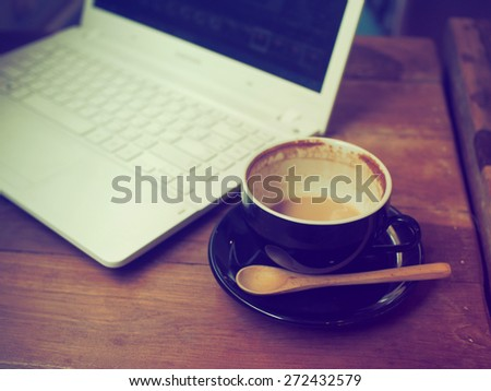cup of coffee latte art and computer laptop on the wood desk