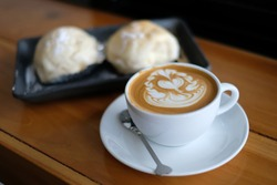 Cup of coffee latte with beautiful latte art and two bread on black dish in the morning. Coffee and bread for breakfast in the morning. Coffee drink concept.