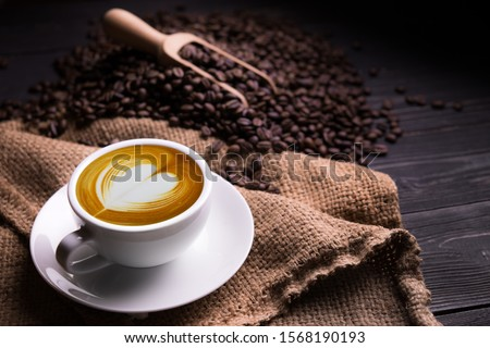Cup of coffee latte with heart shape and coffee beans on old wooden background