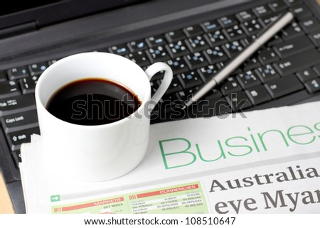 Cup of Coffee, Newspaper and Pen On Laptop - stock photo