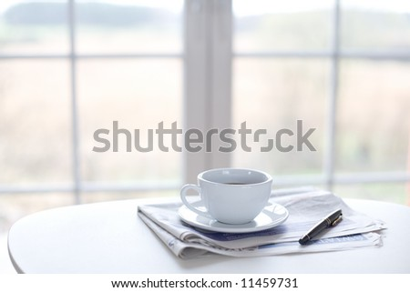 Cup of coffee, newspaper and pen on the table in front of window