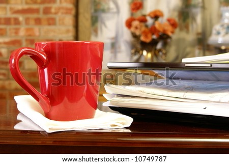 Cup of coffee next to a laptop stuffed with paper work.