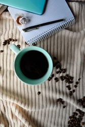 cup of coffee next to notebook with mobile phone and pen on it