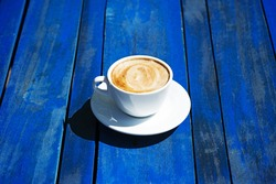 Cup of coffee on a bright wooden table background
