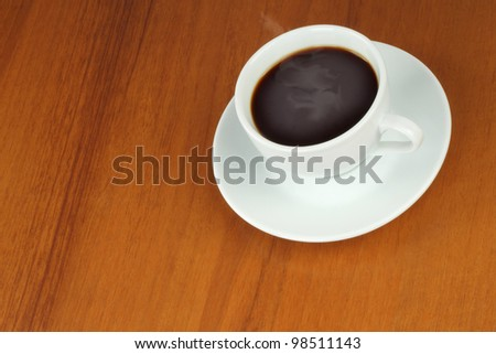 Cup of coffee on a brown wooden background