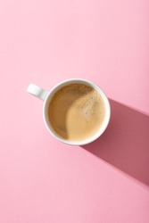 cup of coffee on a pastel pink background, top view, photography with contrast shadow