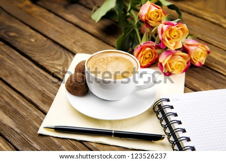 cup of coffee on a wooden table, notebook, notepad to write a bunch of roses, chocolate truffle