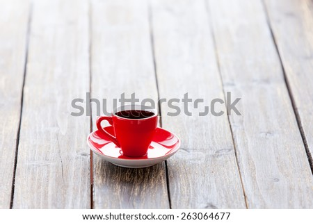 Cup of coffee on a wooden table. Side view.