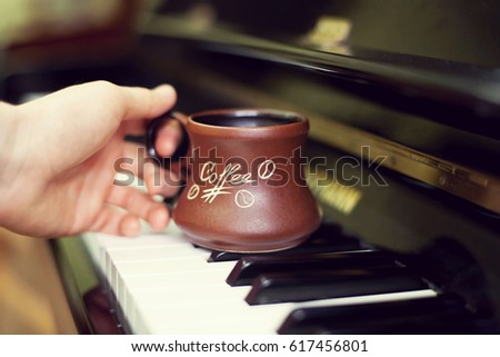 Cup of coffee on an old piano keyboard while composing. Evening time and some sun rays. Coffee mug on the piano keyboard #617456801