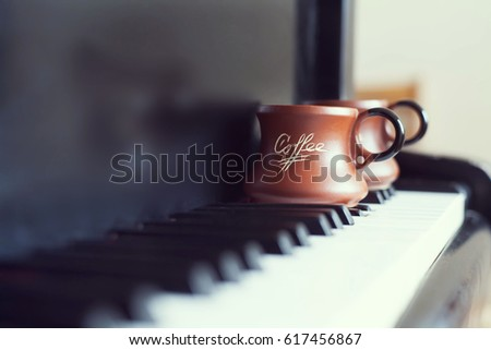 Cup of coffee on an old piano keyboard while composing. Evening time and some sun rays. Coffee mug on the piano keyboard #617456867