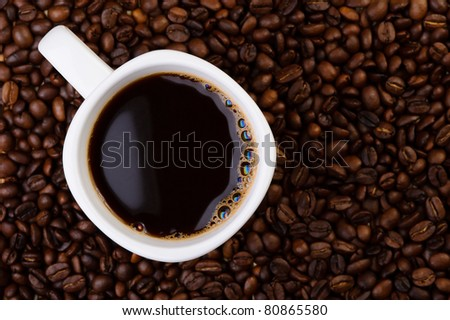 Cup of coffee on aromatic coffee beans. top view