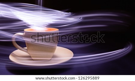 Cup of coffee on black and blue background with light trails above it and around the cup.