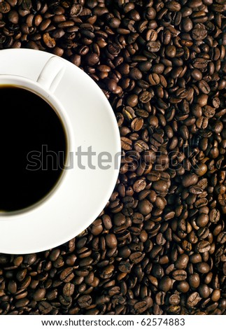 Cup of coffee on coffee beans with uncommon lighting