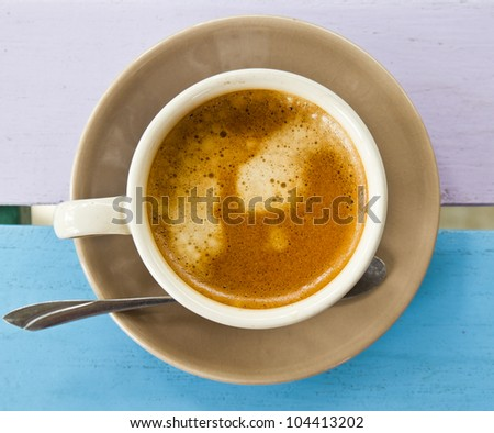 Cup of coffee on color table