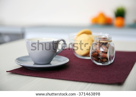 Cup of coffee on cotton napkin in the kitchen, close up