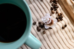 cup of coffee on knitted cloth next to coffee beans