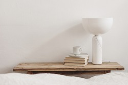 Cup of coffee on pile of books and modern marble geometric lamp. Vintage bench, table. White wall background. Scandinavian interior, bedroom. Selective focus. Blurred bedding. Empty copy space.