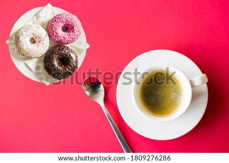 Photo of Cup Of Coffee On Red Background With Three Yummy Donuts.