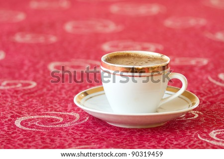 Cup of coffee on red tablecloth