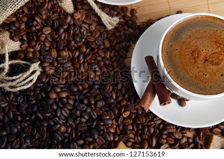 Cup of coffee on saucer and coffee beans