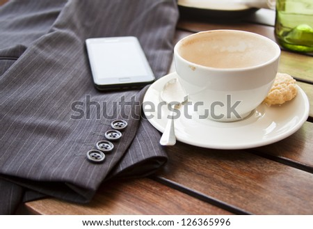 Cup of coffee on table with suit jacket and cell phone in sun concept out of office taking a break mobile office