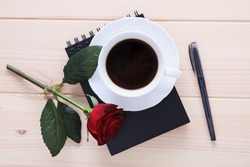 Cup of coffee on the black notepad with red rose and pen at the wooden background top view, romantic, poetic and coffee break theme