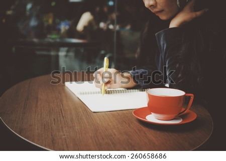 cup of coffee on the desk with woman writing book background in vintage color tone
