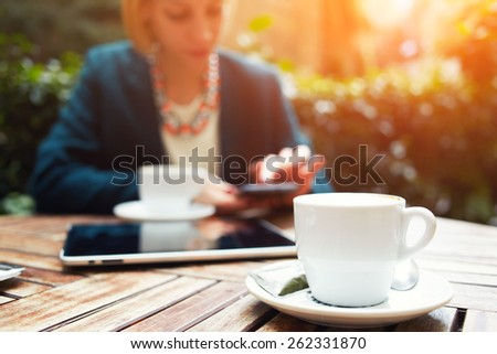 Cup of coffee on the foreground with elegant young woman using busy touch screen tablet at the coffee shop wooden table, work break of business people, flare sun light