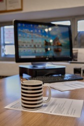 cup of coffee on the table by the computer