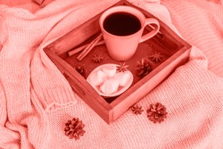 Cup of coffee on tray, marshmallow and warm woolen sweater colored in trendy color of year 2019 Living Coral background. Bright Macro color 16-1546. Hygge morning style concept