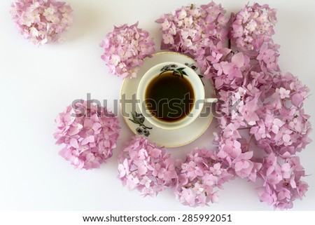 cup of coffee on white background with flowers, cup of coffee on white background with  pink flowers, romantic moment, natural light, view from above