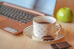 Cup of coffee on wood table with laptop on the background. Piece of black chocolate is on the saucer, coffee pause in the office for refreshment.