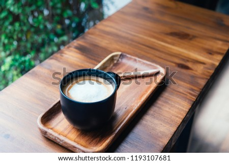 Cup of coffee on wooden table in cafe. Hot latte the best start to any morning.