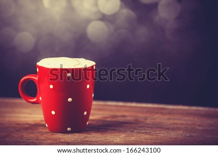 Cup of coffee on wooden table. Photo in old color image style.