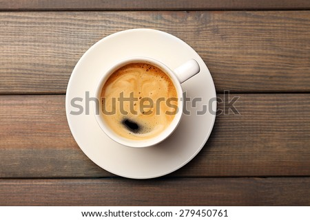 Cup of coffee on wooden table, top view