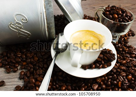 Cup of coffee on wooden table with coffeee beans