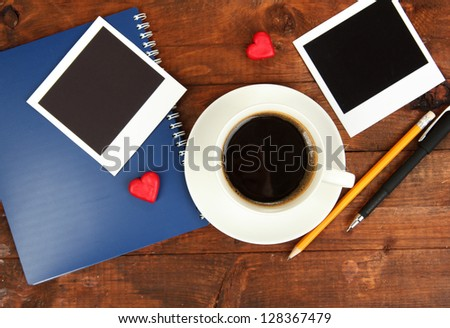 Cup of coffee on worktable covered with photo frames close up