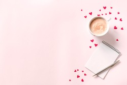 Cup of coffee, open notebook and red hearts on pink beige background, copy space. Minimal flat lay with capuccino coffee and mock up book for Valentine day text, love and romance concept, top view.