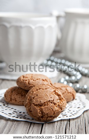 Cup of coffee or tea and almond cookies served on old wooden table