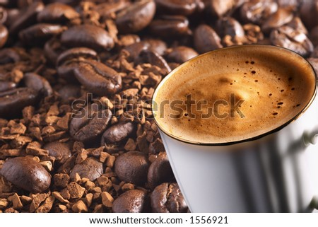 Cup of coffee over coffee-beans and instant coffee background, focus on front rim of cup
