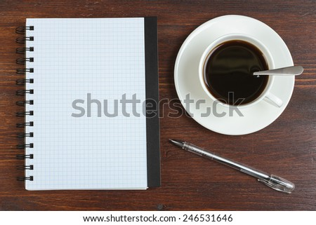 Cup of coffee, pen and opened notepad on desk. Top view