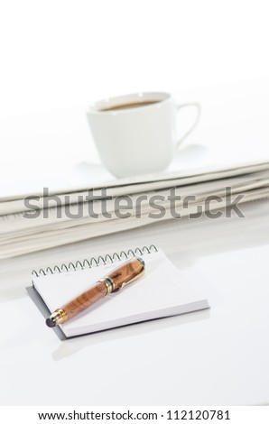 Cup of coffee, pen, notebook and newspaper against a  white background