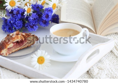 Cup of coffee, piece of kringle with cherry jam, open book and wildflowers - cornflowers and daisies on white wooden tray. #1434740780
