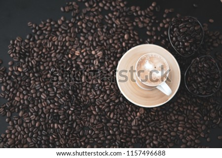 Cup of coffee standing on coffee beans - blurred beans #1157496688