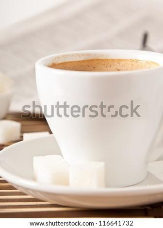cup of coffee, sugar and newspaper closeup